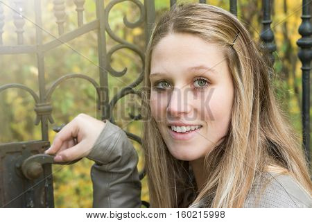 Portrait of long haired young woman standing next to an old iron gate. Woman rests her hand on the doorknob of the gate.