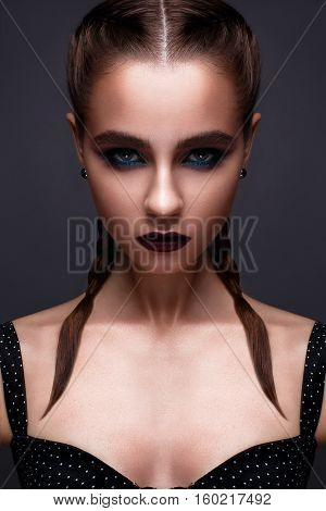Beautiful woman with bright creative make-up. Model with braids and lip color marsala. Beauty face. The photo was taken in a studio. poster