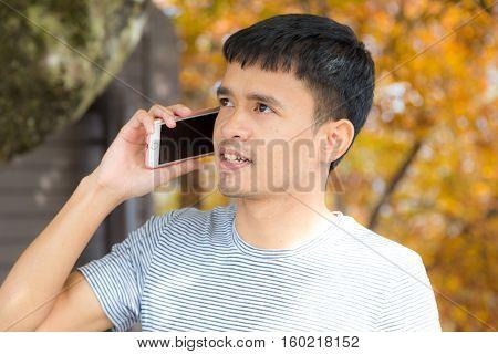 Businessman At Autumn Park Using Mobile Phone