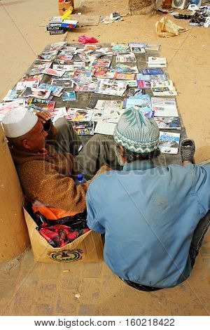 Two male vendors sitting on a floor and selling goods on the market in Tripoli Libia - 25. march 2010