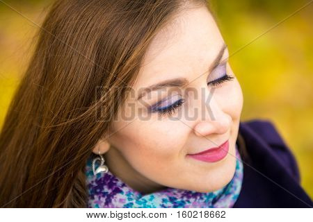 Rub A Beautiful Girl With Closed Eyes On A Blurred Background Of Autumn Leaves