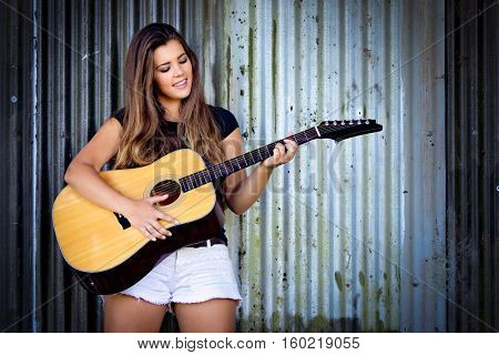 Beautiful smiling girl playing guitar