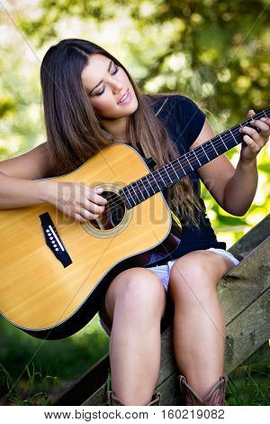 Beautiful woman playing guitar outside