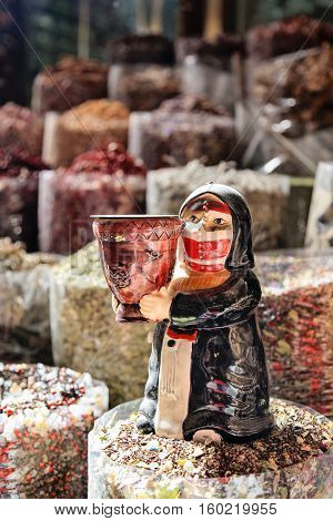 Deira Dubai Spice Souk view on the bags filled with spices, at the front statuette of arabic woman holding wooden vase