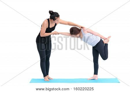 Smiling girl practicing yoga poses and her instructor in yoga class
