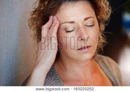 Older Woman With Hand To Head In Pain