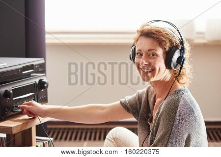 Older Woman Sitting Next To Sound System With  Headphones