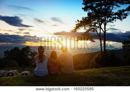 Asian family seat on the top of mountain and look at sunset Family travel concept