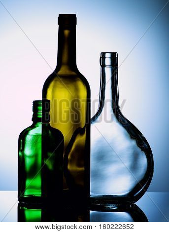 Arrangement of Empty Wine and Cognac Colored Bottles with Reflection on Glass and Shadow Toned Backlight