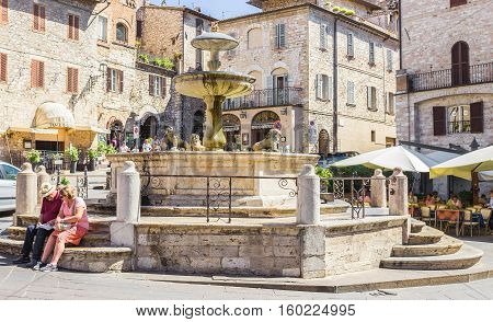 ASSISI ITALY - SEPTEMBER 4 2016: Couple of tourists sitting at the historic fountain figuring three lions and medieval buildings in the background on Piazza del Comune the main square of Assisi Umbria Italy
