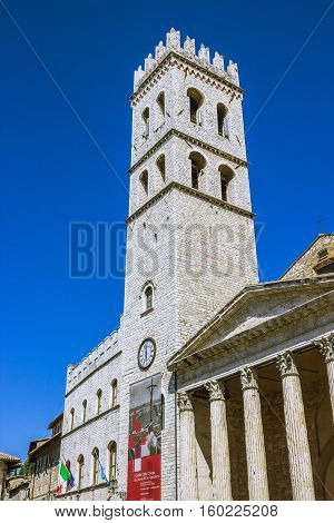 ASSISI ITALY - SEPTEMBER 4 2016: Palace of the People's Captain (Capitano del Popolo) Town Hall tower and the temple of Minerva on the Municipality Square (Piazza del Comune) in the old town of Assisi region of Umbria Italy