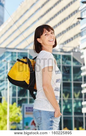 Happy Older Woman Carrying Duffel Bag In City