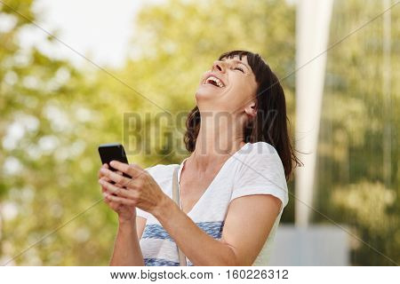 Laughing Older Woman Holding Smart Phone Outside