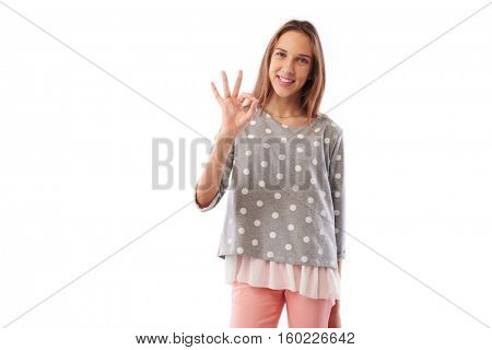 Mid shot of skinny happy toothy smiling young girl showing ok gesture standing over white background. Holding hand on hip while posing at the camera Concept of  nonverbal communication