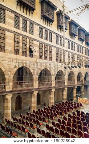 Cairo, Egypt - December 3, 2016: Courtyard of caravansary (Wikala) of al-Ghuri with five floors of vaulted arcades leading to storage rooms and windows covered by interleaved wooden grids (mashrabiya) Medieval Cairo Egypt