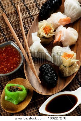 Assorted Dim Sum in Wooden Bowls Red Chili and Soy Sauces and Chopsticks closeup on Straw Mat background