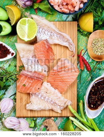 Arrangement of Raw Ingredients of Thai Fish Cakes with Vegetables Spices Herbs Fruits Prawns and Delicious Fillet of Salmon and Cod closeup on Cracked Wooden background