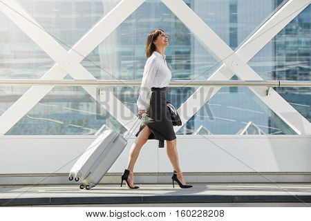 Business Woman Walking With Suitcase In Terminal