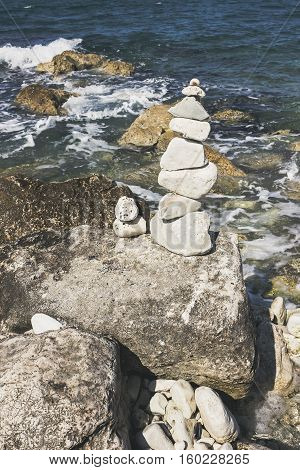 Stones tower on pebble beach with Adriatia Sea in the background. Concept of zen harmony balance.