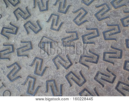 Closeup of cast iron pattern on manhole cover in Alora street in Andalusia