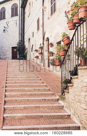 Narrow staircase street of the old town of Assisi with ancient stone houses decorated with flowerpots Italy