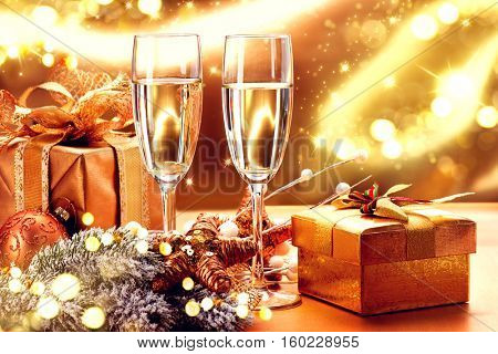 Christmas and New Year Celebration. Two Champagne Glasses and Gifts over Golden Blinking Holiday Background. Christmas party, Winter Holiday party, Xmas