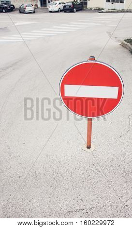 Round red sign No Entry on the street of the european city private houses and car parking on the background