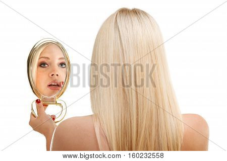 Young woman checking her hair in mirror, isolated at white.