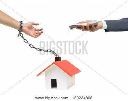 Hand of a businessman offering money to hand chained with a house / Buying a house causing debts concept