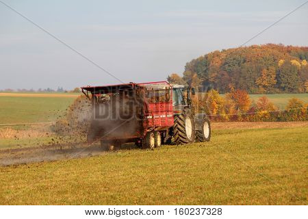 Tractor at work. Tractor spread manure .