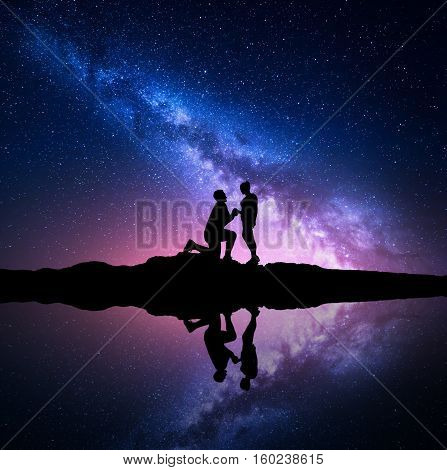 Milky Way. Silhouettes of a man making marriage proposal to his girlfriend on the hill near the lake with starry sky reflection in water. Night landscape. Silhouette of couple. Milky way with people