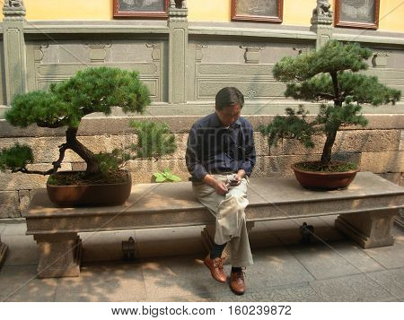 SHANGHAI, CHINA, OCTOBER 05, 2012 - Chinese man sitting between two bonsai inside Jade Buddha temple