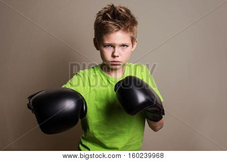 Close up Boxer Boy Wearing Hand Gloves and Looking Fierce at the Camera Against Grey Background. Dangerous Looking Preteen Boxing Fighter.