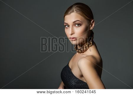 Young woman with plait around her necklace. Horizontal studio shot