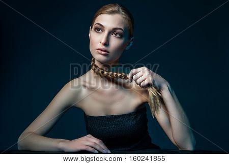 Woman holding plait around her neck. Horizontal studio shot