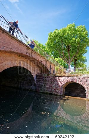Colmar France - May 1 2012: Bridge in Little Venice quarter above River Auch in Colmar Haut Rhin in Alsace France. People on the background