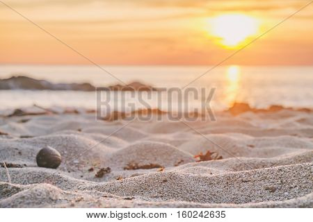 Beautiful seascape. Sea sand with footsteps and rock at the sunset. Nature composition. Thai beach in sunset time in Koh Chang island Thailand. Selective focus