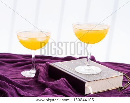 Two Orange Alcohol Cocktails On Purple Textile