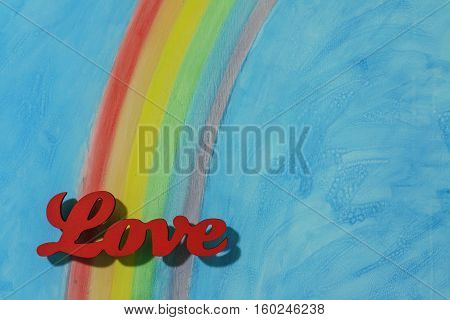 The word love with a background rainbow illustrating the concept of love lust desire and joy; in landscape format