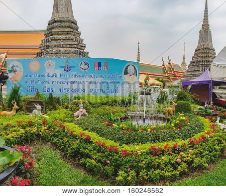 Bangkok, Thailand - January 9, 2016: Temple of Dawn, Wat Arun with beautiful fountain lawn with flowers and statues of the mythical figures