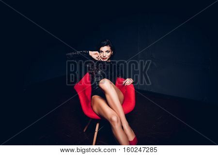 Perfect, sexy body and long legs of young woman wearing seductive lingerie posing in a sensual way in dark room by red modern chair.