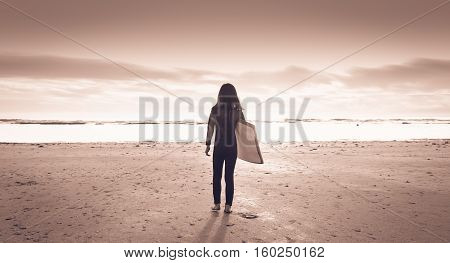 Girl Dressed With A Wetsuit Walking On The Beach