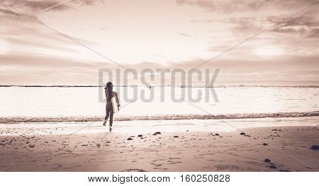 Girl Dressed In A Wetsuit Runs On The Beach