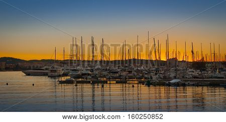 Boats in for the evening in marina harbor under dramatic sunset color .  End of a warm sunny day in Ibiza, St Antoni de Portmany, Spain.