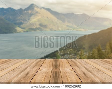Wooden board empty table in front of blurred background. Perspective brown wood table over blur sea and mountain landscape background - can be used mock up for display or montage your products.