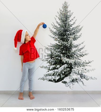 Little boy hanging a decorating ball drawing painting Christmas tree for celebration of Happy new year holiday