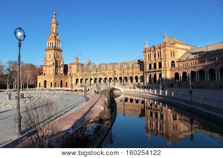 SEVILLE, SPAIN - JANUARY 3, 2012: People walking and making photos on Plaza de Espana. Built in 1928, Plaza de Espana is a landmark example of the Renaissance Revival style in Spanish architecture