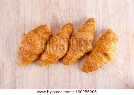 Fresh Croissants On Wooden Table.