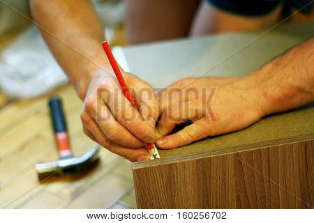 Assembling furniture. The image of a man who with a pencil and a hammer involved in the Assembly of furniture.