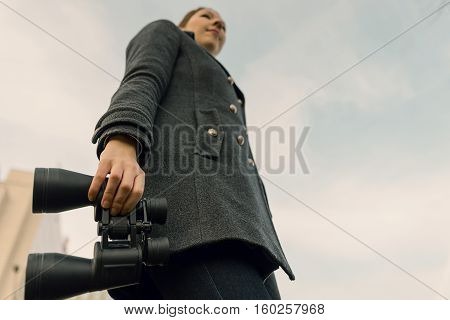 Young Woman With Binoculars Looking Forward. Prospects For Future Business